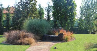 Monolite adibito a panchina attorniato da Carex, Miscanthus ed Imperata cylindrica rubra.